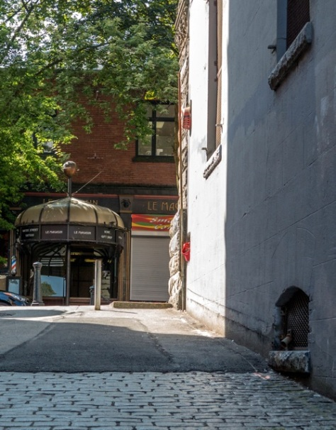 Le Magasin building from (formerly entirely cobblestone) back lane north of Water Street. Author's photo, 2014.