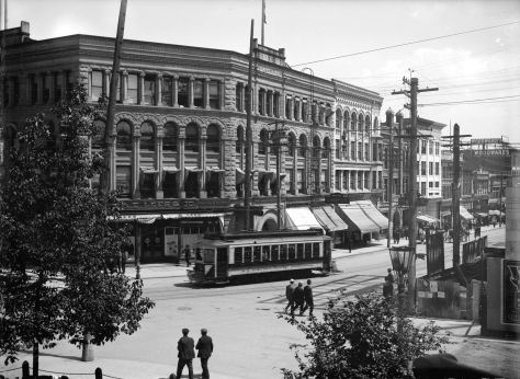 """CVA SGN-924: """"View of Buildings, Streetcars and Pedestrians at Hastings and Cambie Streets."""" 1909."""