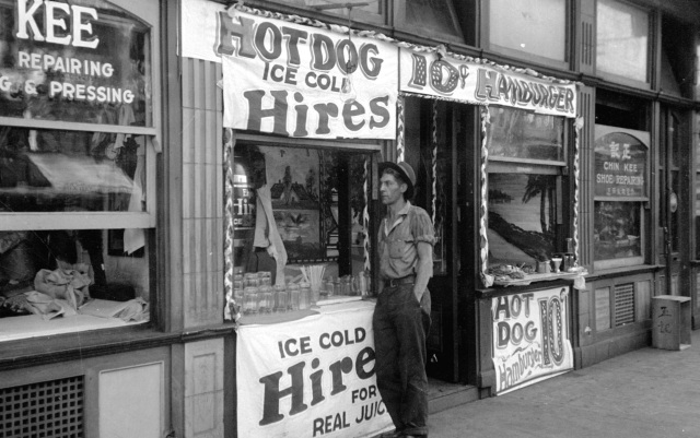 Bu N158.3 - [Man standing outside shallow building at Pender and Carrall Streets], 1936.