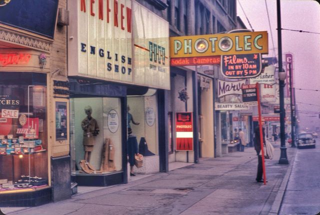 CVA 2009-001.060 - Shops along 600 block Granville Street with Colonial Theatre sign and bus stop. 1965. L F Sheraton