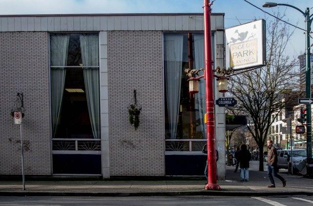 Looking west down East Hastings Street from Columbia Street. Pigeon Park Savings on SW corner Hastings/Columbia, 2015. Author's photo.