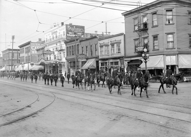 CVA 99-1269 - [Police leading procession on 700 block Main Street]. ca1918. Stuart Thomson photo.