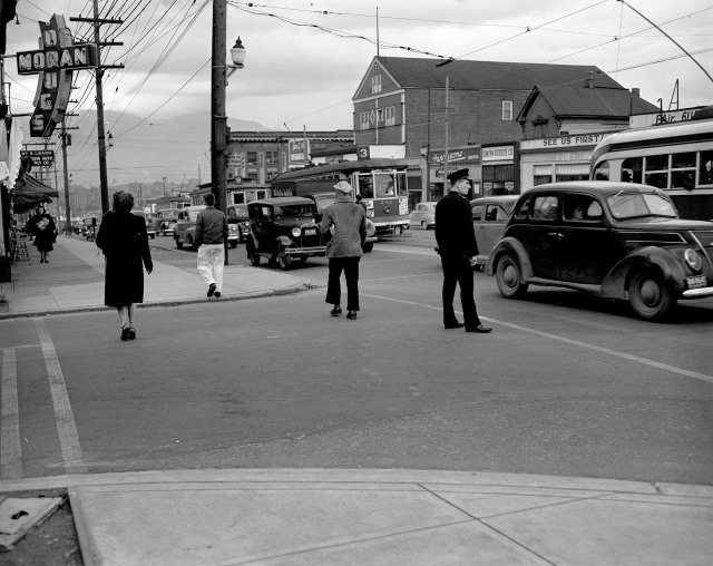 CVA 1184-2769 - Police officer, pedestrians, and traffic, according to CVA on Cambie Street near 12th Avenue -- but I believe it is actually on the 2200 block of Main St. near 6th Ave. Jack Lindsay, 1948?