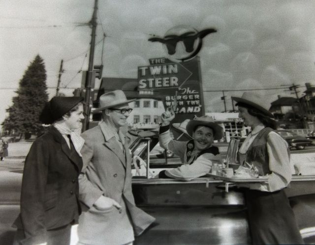 VPL 82512-A Twin Steer Drive-in restaurant, 2805 Cambie Street, convertible automobile, driver, carhop in western costumes, neon sign, twin steers brand on hamburger bun, 1954. Artray photo.