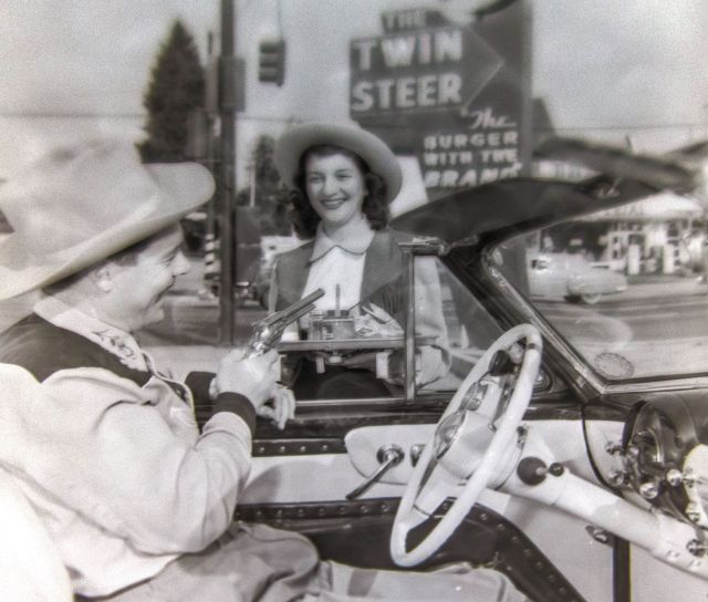 VPL 82512B Twin Steer Drive-in restaurant, 2805 Cambie Street, convertible automobile, driver, carhop in western costumes, neon sign, twin steers brand on hamburger bun, 1954. Artray photo.