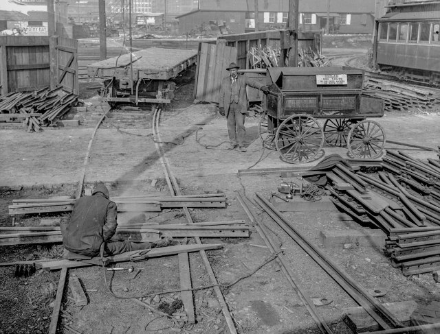 CVA SGN 1068.08 - [Man with generator near man laying streetcar tracks, for reconstruction of Hastings, Main and Harris (Georgia) Street lines] 1912?