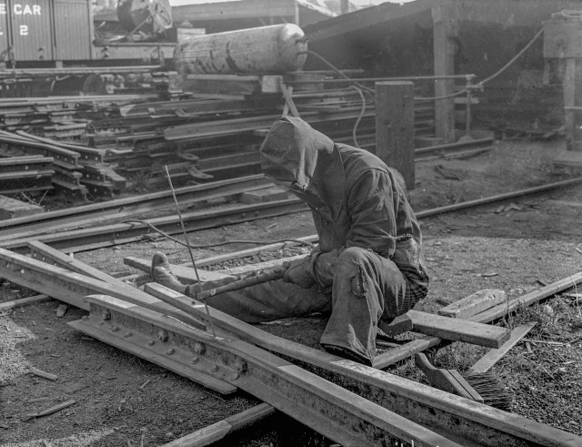 CVA SGN 1068.10 - [Man welding streetcar tracks, for reconstruction of Hastings, Main, and Harris (Georgia) Street lines] 1912? (Note: This seems to be the same welder as in the first image, but taken from his front.)