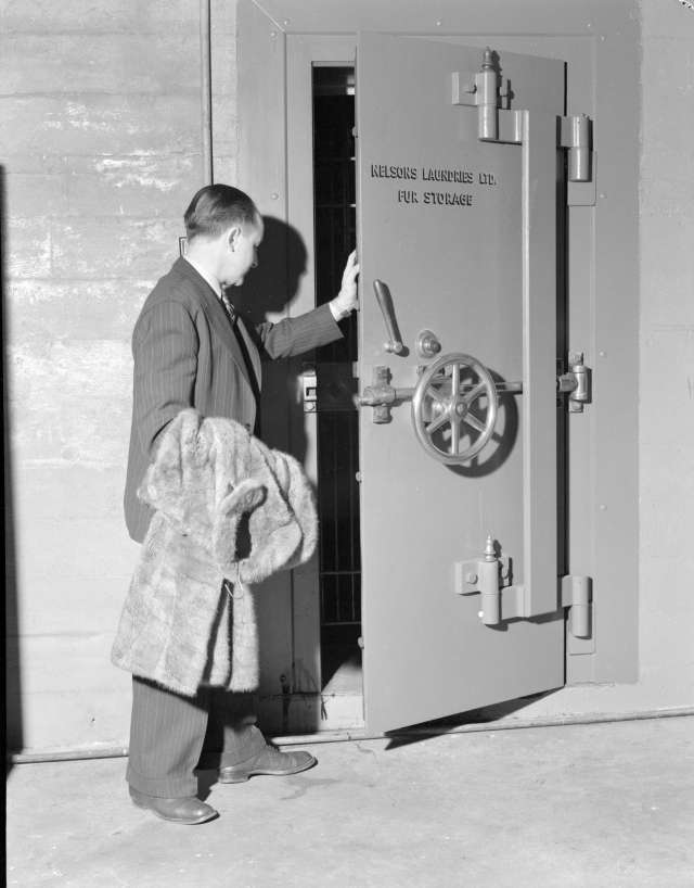 CVA 1184-2244 - [Man with fur coat entering the fur storage vault at Nelsons Laundry] 1940-48 Jack Lindsay photo.