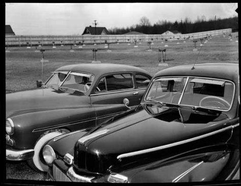 vpl 81172B - Cascade Drive-in Theatre and two automobiles with rain visors. 1950. Artray Studio. Rain visors to be rented for cars attending theatre at 3960 Canada Way, Burnaby.