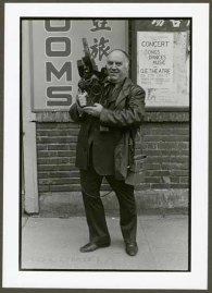 "VPL 88622 ""Man with large camera and microphone in front of signage for rooms"". Nina Raginsky. 1972."