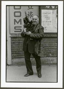 """VPL 88622 """"Man with large camera and microphone (Roy LeBlanc of CBC) in front of signage for rooms"""". Nina Raginsky. 1972."""