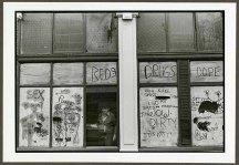 "VPL 88679 ""View of a man through a heavily graffitied window"". Nina Raginsky. 1972."
