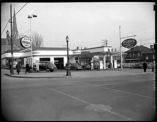 vpl 80449 Black Motors gas station, Georgia & Richards Streets. pumps, cars, sign, Holy Rosary Cathedral 1948 Tom Christopherson photo. Part of a Series 80449-80449D