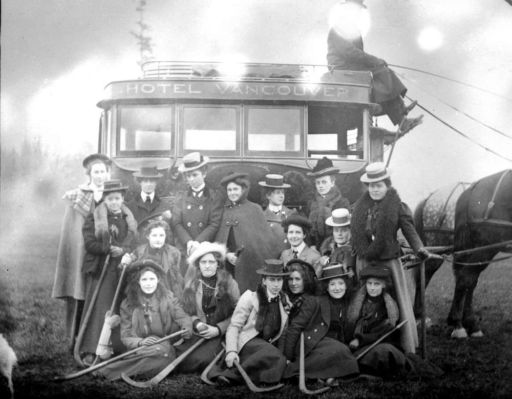 Item B-03482 - Victoria High School girls' grass hockey team; posed with the bus from the Hotel Vancouver during a field trip ca1901
