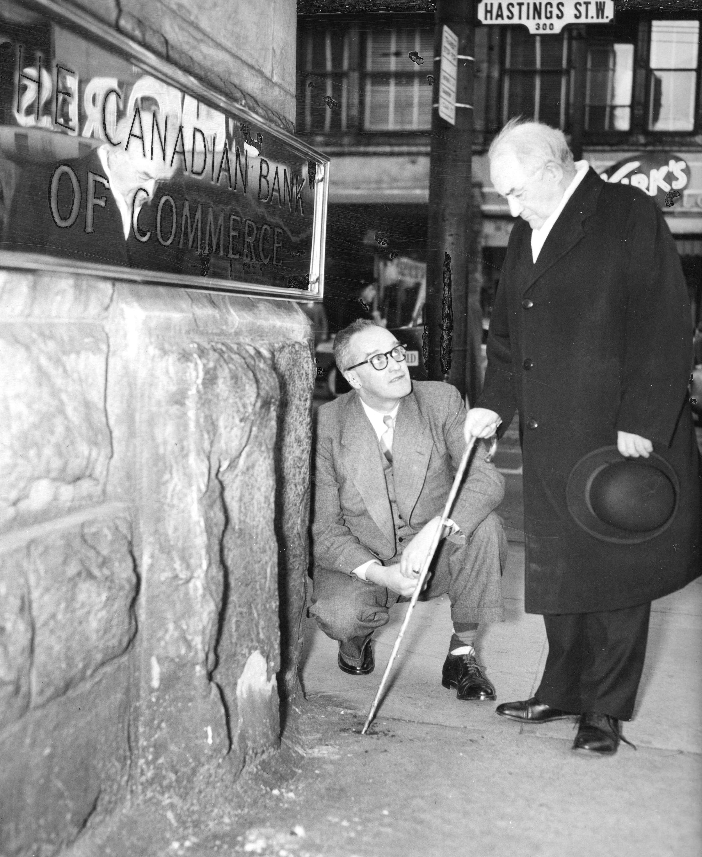 str p306 - [major j.s. matthews and william n. cooper examine the spot where the first survey peg was driven to mark the c.p.r. townsite in 1885] bill cunningham photo, 1953.