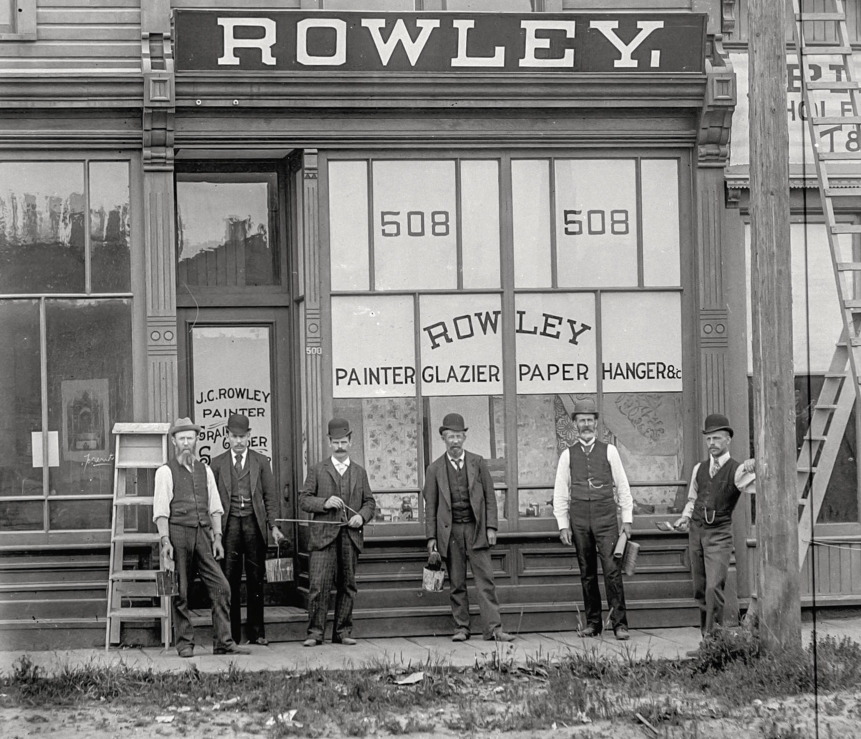 SGN 68 - [Men standing with paint buckets and brushes outside J.C. Rowley House and Sign Painting, 508 West Pender Street] ca 1894