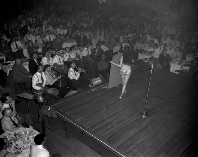 CVA 1184-3471 - [Board of Trade members watching a woman on stage at a Christmas in June luncheon at the Cave cabaret] 1948 Jack Lindsay